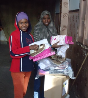 Lailas_daughters_receiving_new_winter_clothes.png